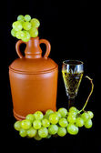 Crystal glass with white wine, bottle and bunch of white grapes on a black cloth — Stock Photo