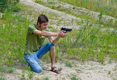 Portrait of a young man taking aim with a pneumatic gun — Stock Photo