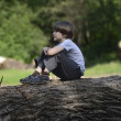 Boy on a log — Stock Photo