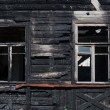 Facade of a wooden house, burnt in the fire — Stock Photo