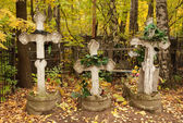 Three graves with crosses rickety and wreaths at the cemetery — Stock Photo