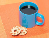 Cup coffee and two cookies on orange napkin — Stock Photo