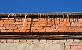 Icicles on the eaves brick building  — Stock Photo