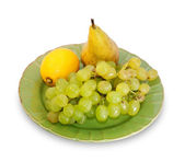 Bunch of grapes, lemon and pear on green plate isolated — Stock Photo