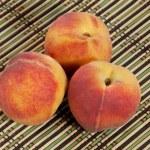 Three ripe red-yellow peaches on wicker straw mat — Stock Photo
