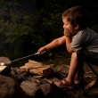 Boy cooking marshmallow - Stock Photo