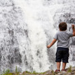 Foto Stock: Boy near a waterfall