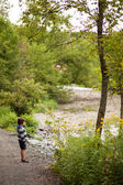Boy standing by a river — Stock Photo