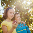 Brother and sister in an orchard — Stock Photo