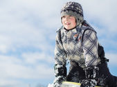 Boy playing in the snow — Stockfoto