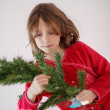 Girl decorating a Christmas tree — Stock fotografie