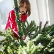 Girl decorating a Christmas tree — Stok fotoğraf