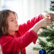 Girl decorating a Christmas tree — Stockfoto