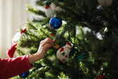 Girl decorating a Christmas tree — Stock Photo