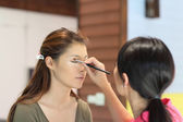 Closeup portrait of a woman having applied makeup by makeup arti — Foto de Stock