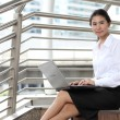 Young businesswoman sitting at stairway and her computer with sm — Stock Photo
