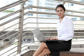 Young businesswoman sitting at stairway and her computer with sm — Photo