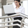 Young businesswoman working with her laptop on handrail — Stock Photo #35710739