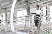 Young businesswoman working with her laptop on handrail — Stock Photo