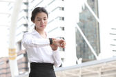 Business woman checking the time with modern building background — Stock Photo