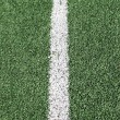 图库照片: Photo of a green synthetic grass sports field with white line sh