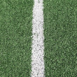 Photo of a green synthetic grass sports field with white line sh — Foto de Stock