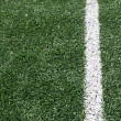 Photo of a green synthetic grass sports field with white line — Foto de Stock