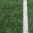 Photo of a green synthetic grass sports field with white line — Stock Photo