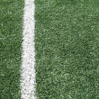 Photo of a green synthetic grass sports field with white line sh — Zdjęcie stockowe