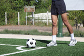 Soccer ball with his feet on the football field — Stock Photo