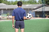 Back of a football referee holding the ball — Stock Photo