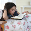 Charming woman reading a book sitting on a sofa in a living-room — Stock Photo