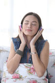 Young woman listening music through headphones, eyes closed.  — Stock Photo