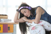 Young woman relaxing on an armchair at home, listening to music — Stock Photo