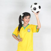 Beautiful woman hold ball over her head with wearing Brazil foot — Stock Photo