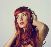 Redhead girl with headphones — Stock Photo