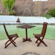 Stock Photo: Table and chairs near pool