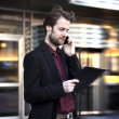 Forty years old businessman standing outside modern office building talking on a mobile phone — Stock Photo