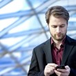 Forty years old businessman standing inside modern office building looking on a mobile phone — Stock Photo