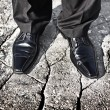 Businessman legs standing on a cracked ground - uncertain future, insecure situation or risky investment decision concept — Stock Photo #22967622