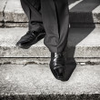 Businessman legs taking step on a lower level on a stairs - bad investment decision concept — Stock Photo #22967630