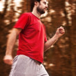 Forty years old man during a running workout in autumn forest - Stockfoto