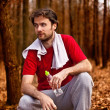 Forty years old runner man drinking water and having a rest after jogging workout in autumn forest — Stock Photo