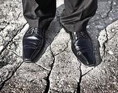 Gambe di uomo d'affari in piedi su un terreno di cracking - incerta situazione futura, insicura o concetto di decisione di investimento rischioso — Foto Stock