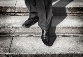 Businessman legs taking step on a lower level on a stairs - bad investment decision concept — Stock Photo