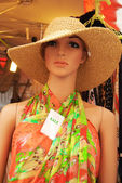 Woman mannequin dressed in a colourful summer dress and a straw — Stock Photo