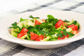 Green fresh salad in a rustic plate served on a checked tableclo — Stock Photo