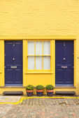 Porch with dark blue doors, yellow bricks and white windows. — Stock Photo