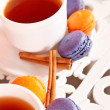 Tecup with purple and orange macaroons and canella — Stock Photo #22976372