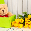 Present teddy bear and yellow tulips flower — Stock Photo